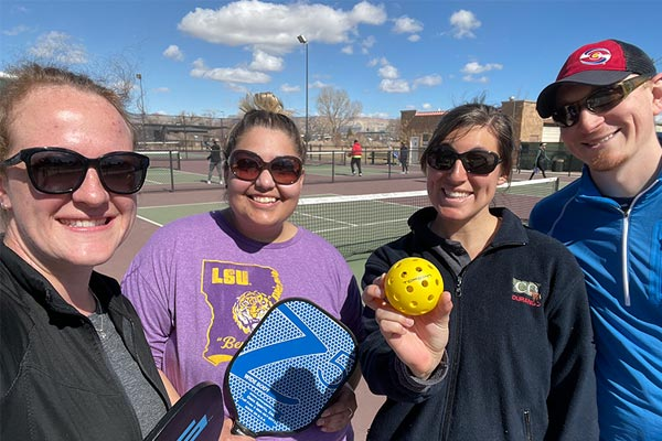 Editor Cloie Sandlin poses with friends holding a pickleball racket and ball