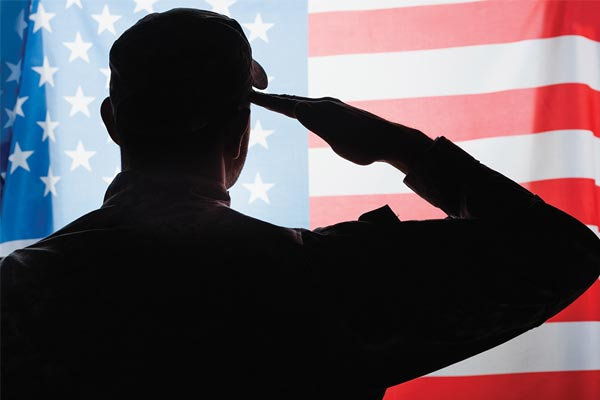 Silhouette of man saluting an American flag, which fills the background