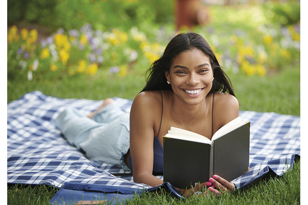 Young women laying on a blanket in the grass reading a book