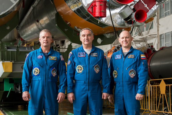 The crew poses in front of the engines of their spacecraft. (#9)