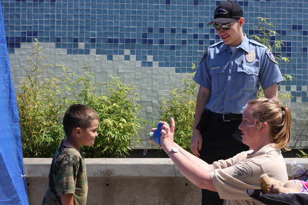 A young boy smiles for the camera as volunteers take his photo during the police department's child safety event.