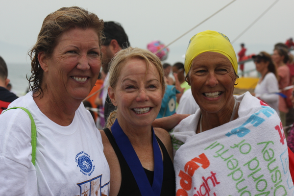 (Left to right) Anne Ozer, Peggy Sullivan and Anne Dawson celebrate their completion of the Dwight Crum Pier to Pier Swim on the sand near Manhattan Beach Pier.